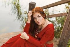 Retrato de la mujer seria joven en vestido rojo cerca del río Imagen de archivo
