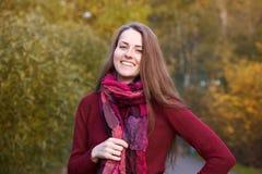 Retrato de la mujer sonriente alegre que camina en parque del otoño en un s Fotos de archivo
