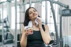 Retrato de la mujer sonriente de la aptitud con el vaso de agua con el limón, mujer en ropa de deportes después del agua potable  foto de archivo