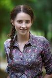 Retrato de la mujer sonriente atractiva joven en el parque del verde del verano en un día soleado Fotos de archivo