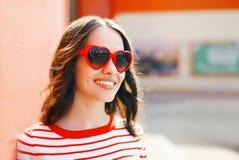 Retrato de la mujer sonriente bonita en gafas de sol rojas Imagenes de archivo