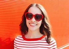Retrato de la mujer sonriente bonita en gafas de sol rojas Foto de archivo