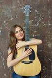 Retrato de la mujer sonriente con la guitarra acústica Imagenes de archivo