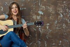 Retrato de la mujer sonriente con la guitarra acústica Imágenes de archivo libres de regalías