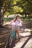 Retrato de la mujer sonriente con la bicicleta Foto de archivo libre de regalías