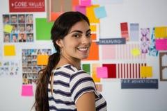 Retrato de la mujer sonriente contra notas pegajosas en oficina Imágenes de archivo libres de regalías