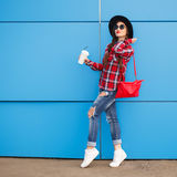 Retrato de la mujer sonriente de la moda de la belleza con café en gafas de sol en fondo azul outdoor Copyspace Fotografía de archivo libre de regalías