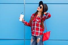 Retrato de la mujer sonriente de la moda de la belleza con café en gafas de sol y sombrero negro en fondo azul outdoor Copia-espa Imagenes de archivo