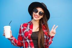 Retrato de la mujer sonriente de la moda de la belleza con café, haciendo las paces por los fingeres en gafas de sol en fondo azu Imagen de archivo