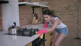 Retrato de la mujer sonriente del ama de casa en los guantes de goma durante la limpieza general de las tareas de la cocina y de  almacen de video
