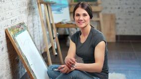 Retrato de la mujer sonriente del artista que presenta en el estudio del arte que mira el tiro medio de la c?mara metrajes