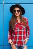 Retrato de la mujer sonriente del inconformista en sombrero negro y de sunglasess en la pared azul outdoor Imagen de archivo libre de regalías