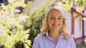 Retrato de la mujer sonriente feliz en el jardín del verano almacen de metraje de vídeo