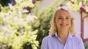 Retrato de la mujer sonriente feliz en el jardín del verano metrajes