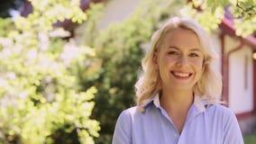Retrato de la mujer sonriente feliz en el jardín del verano almacen de video