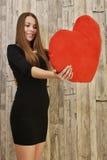 Retrato de la mujer sonriente hermosa con el corazón rojo Imagenes de archivo