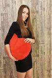 Retrato de la mujer sonriente hermosa con el corazón rojo Imagen de archivo