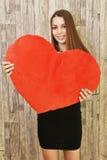 Retrato de la mujer sonriente hermosa con el corazón rojo Foto de archivo