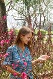 Retrato de la mujer sonriente hermosa joven con el pelo rubio en un jardín con los árboles florecientes imagenes de archivo