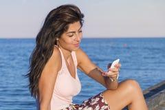 Retrato de la mujer sonriente hermosa que habla en el teléfono que se sienta en un embarcadero del mar Imagen de archivo