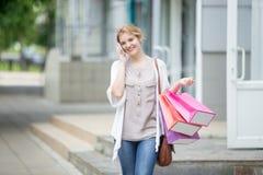 Retrato de la mujer sonriente joven en el teléfono móvil durante compras Fotografía de archivo libre de regalías