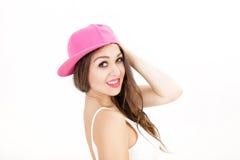 Retrato de la mujer sonriente joven en la camisa blanca y el sombrero rosado en el fondo blanco Imagenes de archivo