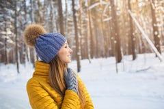 Retrato de la mujer sonriente joven en la ropa brillante que mira a un lado en un bosque Imagen de archivo libre de regalías