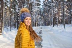Retrato de la mujer sonriente joven en la ropa brillante que se coloca en un bosque Foto de archivo libre de regalías