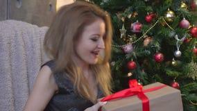 Retrato de la mujer sonriente joven en sala de estar adornada con los regalos y el árbol de navidad almacen de video