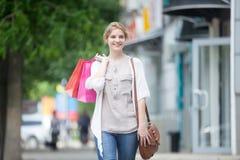 Retrato de la mujer sonriente joven que disfruta de tiempo que hace compras Imágenes de archivo libres de regalías