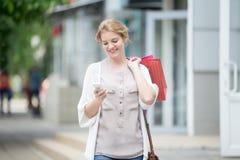 Retrato de la mujer sonriente joven que mira el teléfono mientras que va para Fotos de archivo