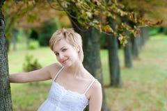 Retrato de la mujer sonriente joven que presenta cerca del tr Fotos de archivo