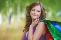 Retrato de la mujer sonriente joven que sostiene muchos bolsos Imagen de archivo libre de regalías
