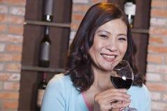 Retrato de la mujer sonriente madura que goza de un vidrio de vino Imagen de archivo libre de regalías
