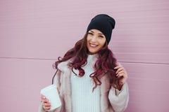 Retrato de la mujer sonriente de la moda de la belleza con café en capa de visión y sombrero negro en fondo rosado outdoor Fotos de archivo