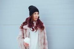 Retrato de la mujer sonriente de la moda de la belleza con el café que muestra la lengua en capa de visión y sombrero negro en fo Foto de archivo