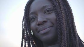 Retrato de la mujer sonriente negra joven afroamericana confiada en el fondo del cielo y de la calle metrajes