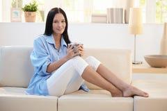 Retrato de la mujer sonriente que come café en el sofá Foto de archivo