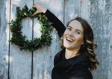 Retrato de la mujer sonriente que cuelga una guirnalda de la Navidad en su hogar Imagen de archivo