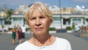 Retrato de la mujer sonriente que se coloca al aire libre de mirada de la cámara Pensionista que viaja en Moscú, Rusia almacen de video