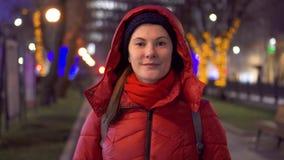 Retrato de la mujer sonriente que se coloca en calle con los árboles adornados con las guirnaldas La Navidad del Año Nuevo metrajes