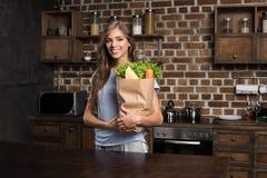 retrato de la mujer sonriente que sostiene la bolsa de papel llena de comida mientras que se coloca fotografía de archivo libre de regalías