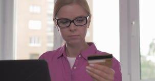 Retrato de la mujer sonriente que sostiene la tarjeta de crédito en su mano mientras que hace compras en línea metrajes