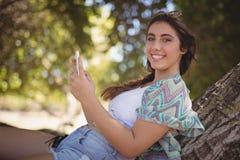 Retrato de la mujer sonriente que usa el teléfono elegante Imagen de archivo
