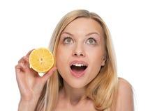 Retrato de la mujer sorprendida con el limón que mira en espacio de la copia Fotografía de archivo
