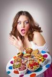Retrato de la mujer sorprendida joven que come las tortas Foto de archivo