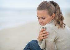 Retrato de la mujer tranquila que se sienta en la playa fría Foto de archivo libre de regalías