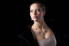 Retrato de la mujer en abrigo de pieles negro con joyería Fotos de archivo