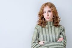 Retrato de la mujer triste agravada con el pelo rojo largo con las manos cruzadas que expresan su descontento y disconent Imagenes de archivo