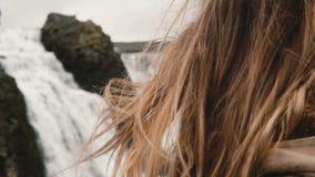 Retrato de la mujer triste hermosa joven que se coloca cerca de la cascada en Islandia y que mira alrededor Pelo que agita en el  almacen de video